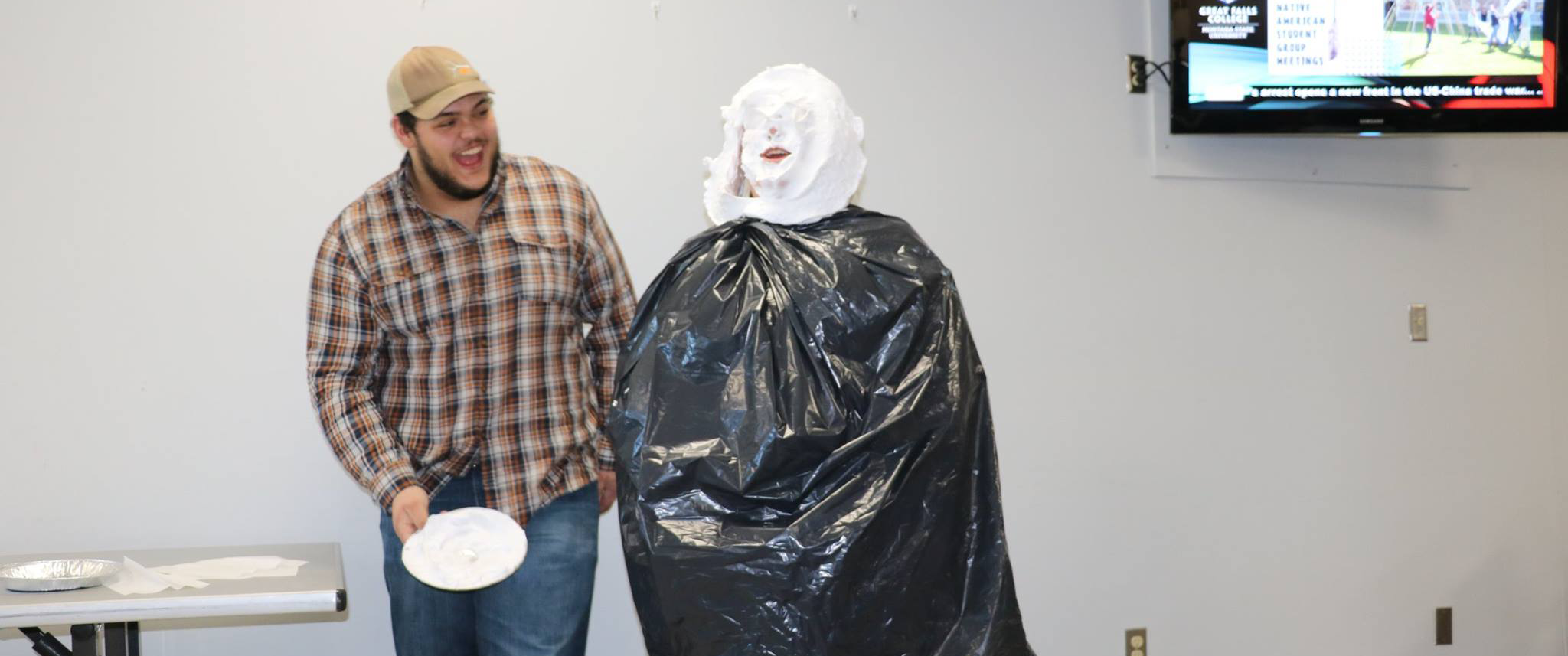 Griz Representatives prepare to get a pie in the face from their Cats counterparts for raising less food for the drive.